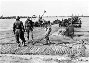 """Mulberry Artificial Harbor: Black American soldiers construct landing ramp at Mulberry """"A"""""""