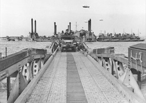 """Mulberry Artificial Harbor: Army truck traverses Mulberry """"A""""'s """"Whale"""" floating roadway"""
