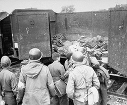 Hitler youth examine boxcars of dead at Dachau
