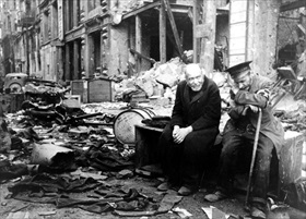 Two elderly men seated amid street rubble, Berlin, 1945