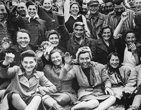Female prisoners at Dachau smile and wave