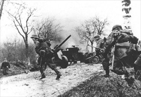 Ardennes Offensive: German troops advance past abandoned American equipment