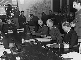 German unconditional surrender, Reims, France, May 7, 1945. Oxenius (left), Jodl (signing), Friedeburg