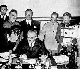 Molotov signs 1939 pact overseen by Ribbentrop and Stalin