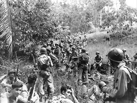 Men from 2nd Marine Division, pursuing retreating Japanese, stop for a rest, November 1942