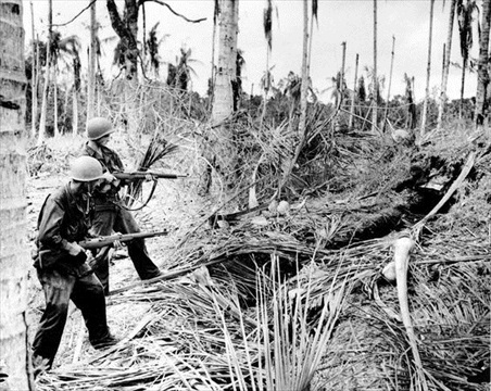 New Guinea Campaign: 32nd Division soldiers fire into Japanese dugout near Buna, New Guinea