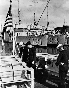 """Royal Navy and U.S. Navy sailors inspect depth charges aboard """"Wickes""""-class destroyers, 1940"""
