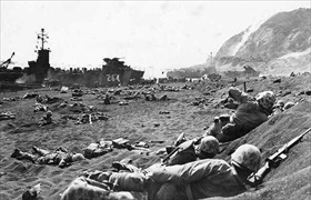 Marines seek cover on Iwo Jima beach, February 21 or 22, 1945