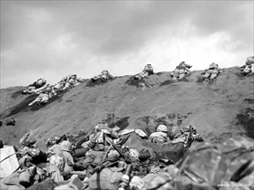 Marines inch their way up a slope toward Mt. Suribachi