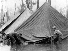 Battle of Cape Gloucester: Marines try erecting a tent at Cape Gloucester base camp during a monsoon deluge