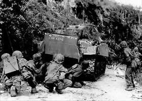 Marines take cover behind M4 tank, Saipan, July 8, 1944
