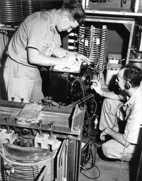 OWI personnel adjusting KSAI radio transmitter