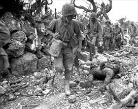 Marines pass dead Japanese soldier, Okinawa, April 1945