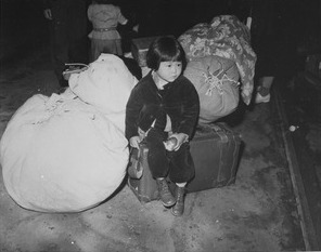 Executive Order 9066: Young Japanese American evacuee and baggage, Spring 1942
